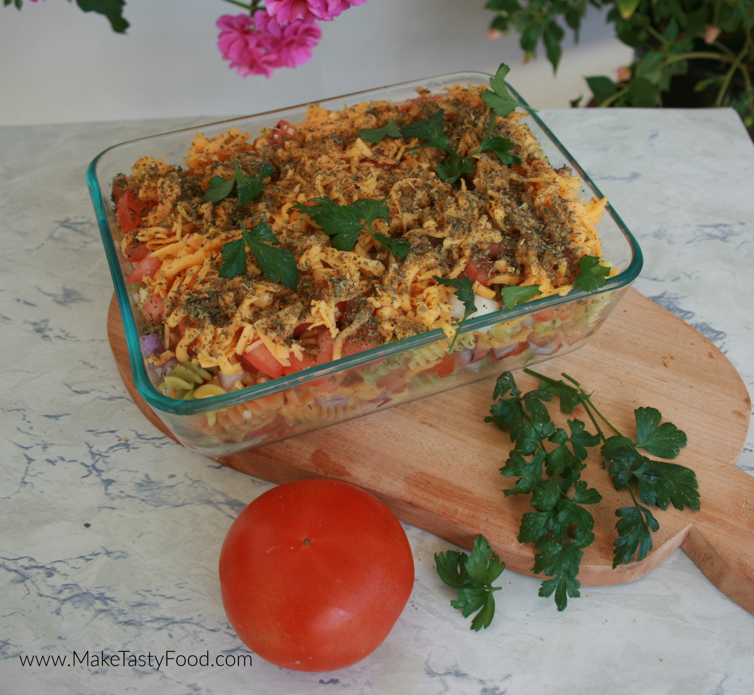 The dish layered with pasta and tomato and cheese ready to have the egg and milk poured in.