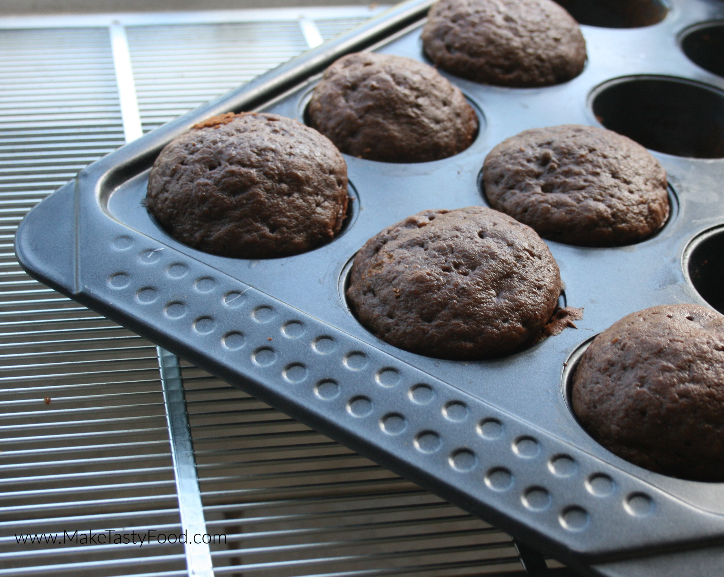 a muffin pan filled with chocolate banana muffins