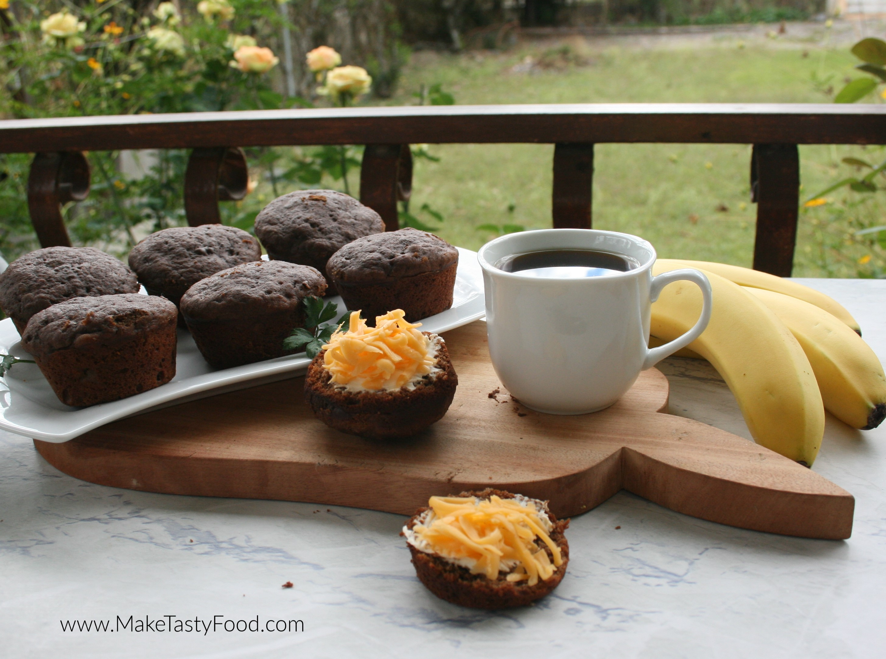 some coffee and chocolate muffins made with banana plated and cheese and butter on half of muffins