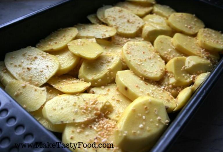 layered potatos and garlic in a roasting pan