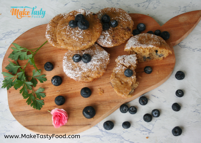 tasty banana blueberry muffins plated on a bread board with scattered blueberries