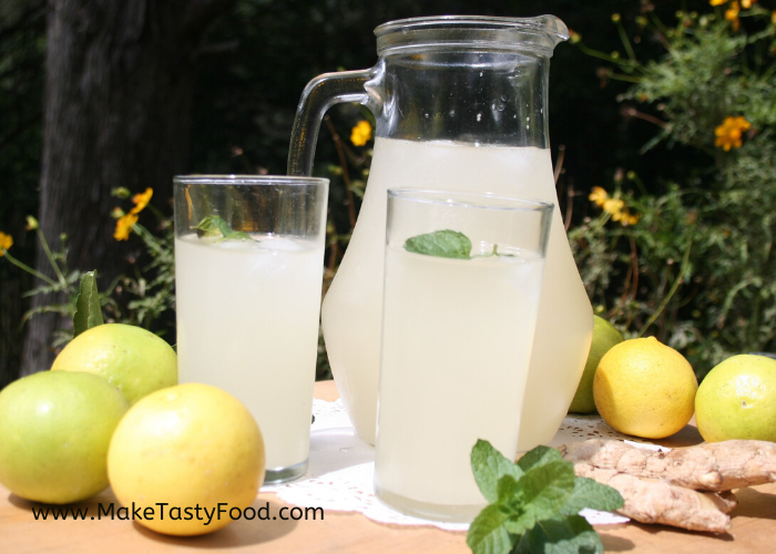 two glasses of ginger beer and a jug full of lemon and ginger beer