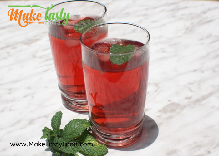 two glasses of berry fruit red iced tea with ice and mint leaves