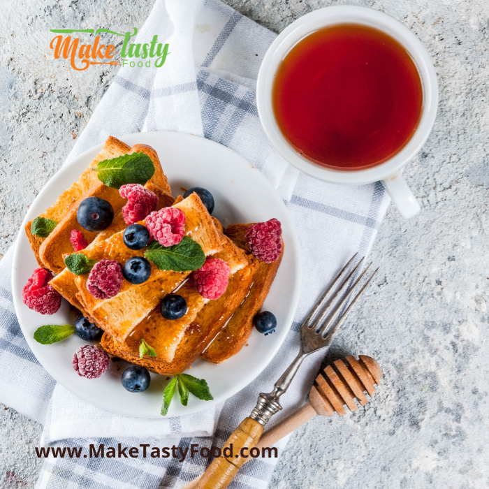 a breakfast fit for a king french toast and berries and drizzled honey and coffee