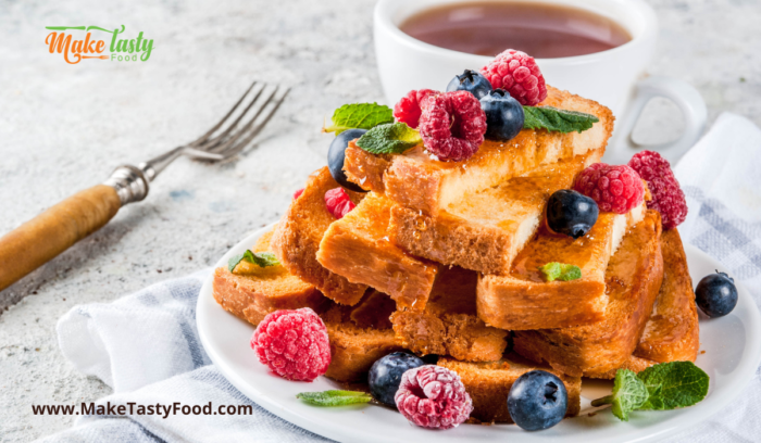 A plate of french toast pieces with berries and honey and coffee for breakfast for a special occasion
