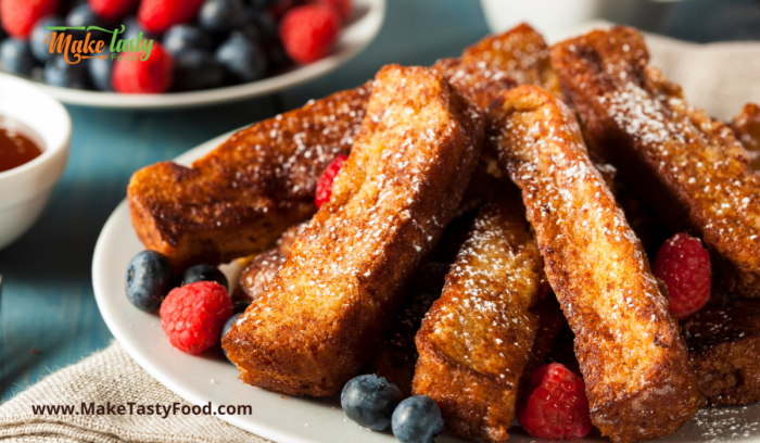 french toast on a plate with berries and drizzled honey