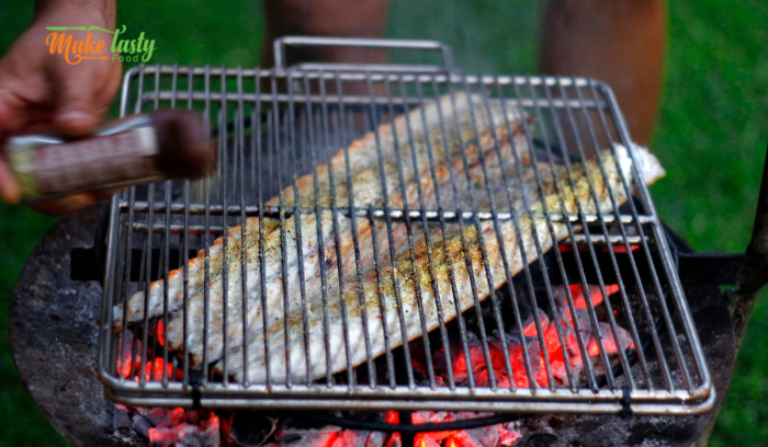 Salt and peppering the cut up snoek fish on a grill on coals