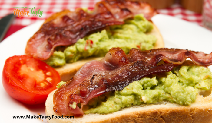 toast with mashed avocado and fried bacon and tomato for breakfast