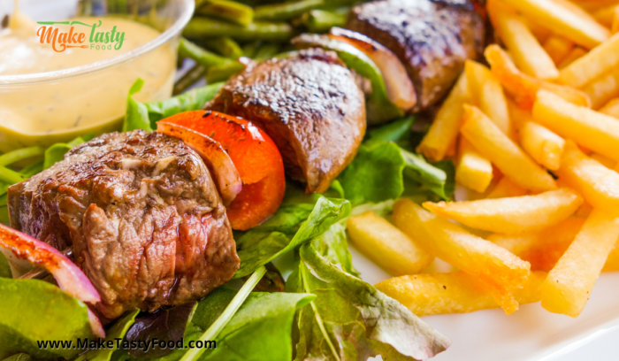 A grilled beef and peppers sosatie or kabab with salad and chips