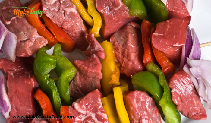 made beef and peppers and onion sosatie that are uncooked and ready to marinate.