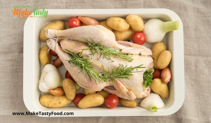 a roasing dish filled with a chicken and potato's and herbs and fennel ready  to roast.