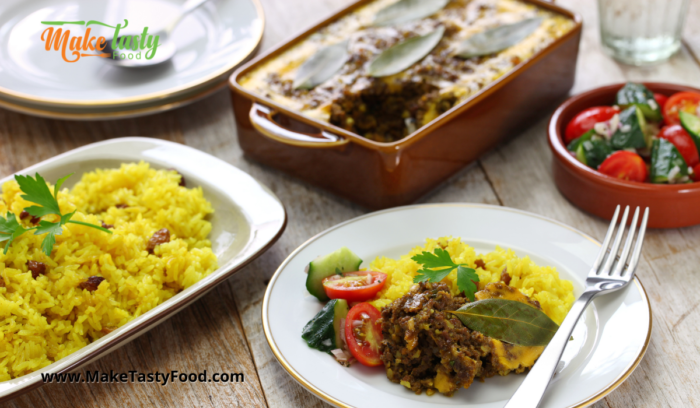 a casserole of bobotie and yellow rice with salad for a meal