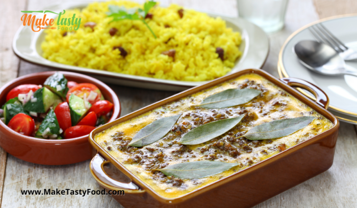 a bobotie dish baked with yellow rice and salad