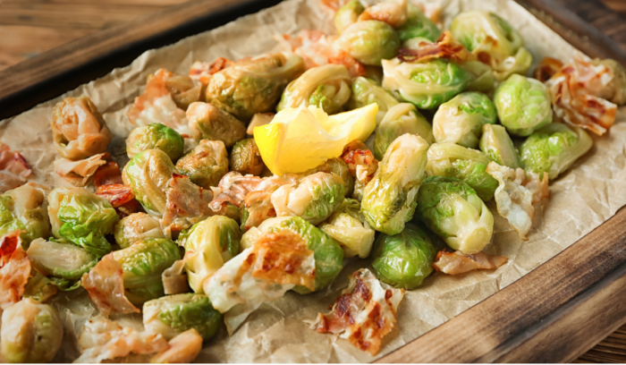 placing brussel sprouts and ingredients on a baking pan to roast